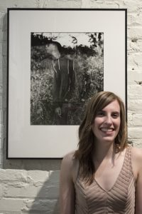 Alison posing in front of a photo at her Area 31 exhibition opening in Frederick, MD.